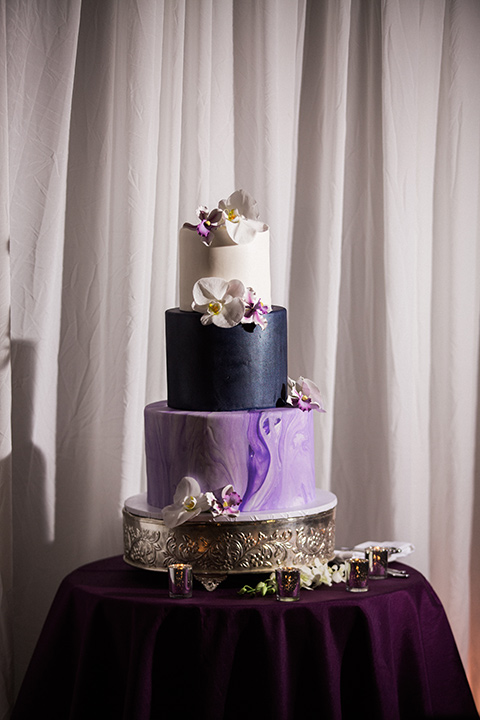 Avenue-of-the-arts-wedding-cake-three-tiers-with-different-purple-fondant-and-florals