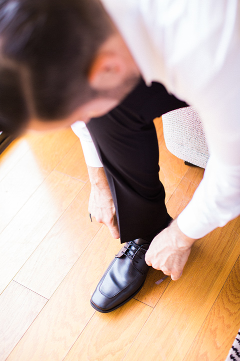 Avenue-of-the-arts-wedding-groom-tying-shoes-groom-inblack-tuxedo-with-a-silver-vest-and-silver-bowtie