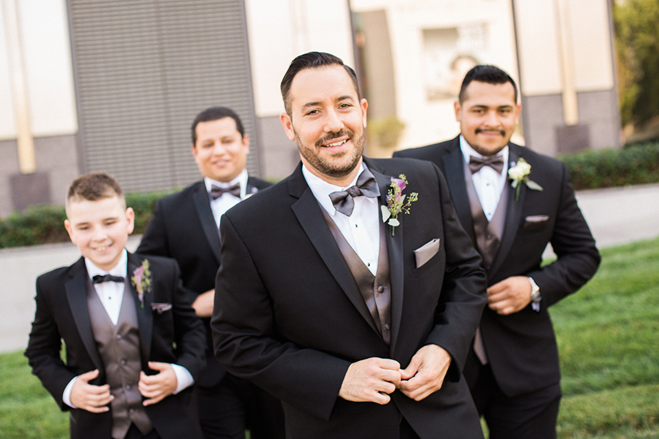 Avenue-of-the-arts-wedding-groomsmen-in-black-tuxedos-with-a-silver-vest-and-silver-bowtie