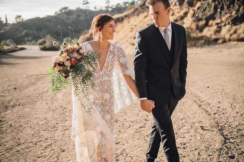 bronson-caves-elopement-shoot-bride-and-groom-walking-bride-wearing-a-lace-boho-inspired-dresswith-a-flowing-cape-detail-and-hair-up-in-a-mess-braided-bun-the-groom-wore-a-navy-suit-with-a-silver-tie
