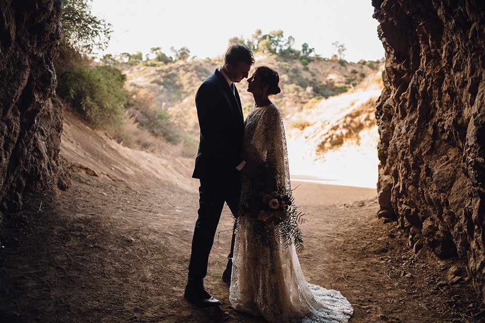 bronson-caves-elopement-shoot-bride-and-groom-in-cave-bride-wearing-a-lace-boho-inspired-dresswith-a-flowing-cape-detail-and-hair-up-in-a-mess-braided-bun-the-groom-wore-a-navy-suit-with-a-silver-tie