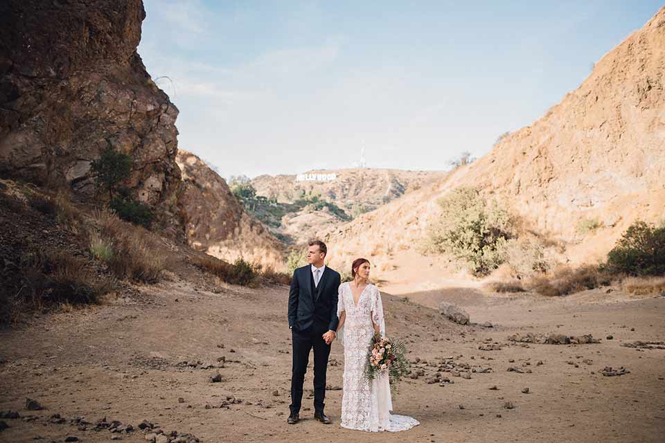 bronson-caves-elopement-shoot-bride-and-groom-looking-in-opposite-directions-bride-wearing-a-lace-boho-inspired-dresswith-a-flowing-cape-detail-and-hair-up-in-a-mess-braided-bun-the-groom-wore-a-navy-suit-with-a-silver-tie
