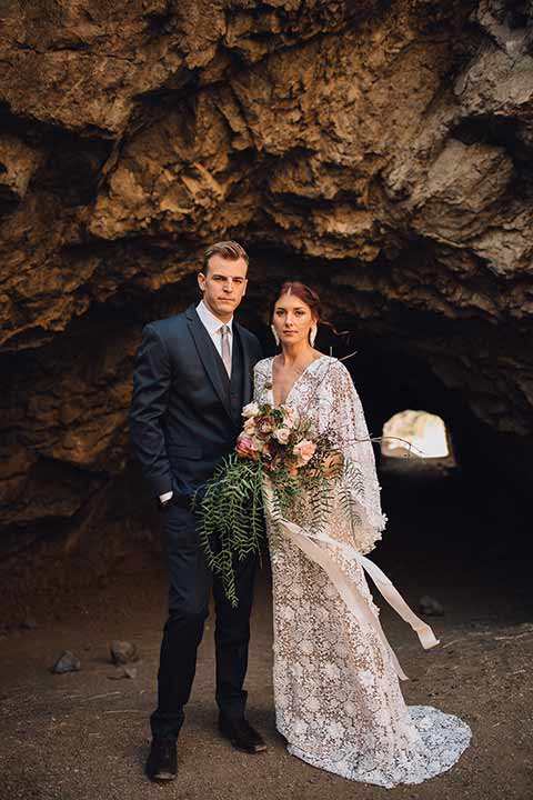 bronson-caves-elopement-shoot-bride-and-groom-outside-of-cave-looking-at-camera-bride-wearing-a-lace-boho-inspired-dresswith-a-flowing-cape-detail-and-hair-up-in-a-mess-braided-bun-the-groom-wore-a-navy-suit-with-a-silver-tie