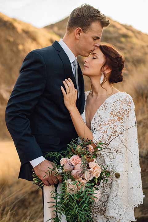 bronson-caves-elopement-shoot-bride-and-groom-with-sunset-behind-them-bride-wearing-a-lace-boho-inspired-dresswith-a-flowing-cape-detail-and-hair-up-in-a-mess-braided-bun-the-groom-wore-a-navy-suit-with-a-silver-tie