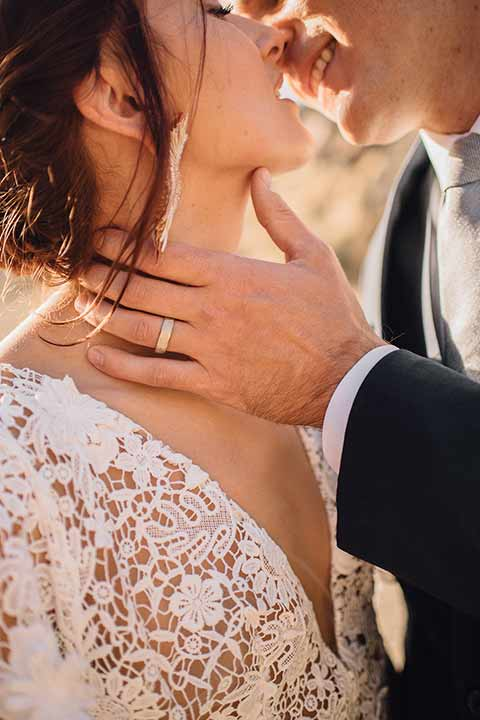 bronson-caves-elopement-shoot-close-up-of-bride-and-groom-kissing-bride-wearing-a-lace-boho-inspired-dresswith-a-flowing-cape-detail-and-hair-up-in-a-mess-braided-bun-the-groom-wore-a-navy-suit-with-a-silver-tie