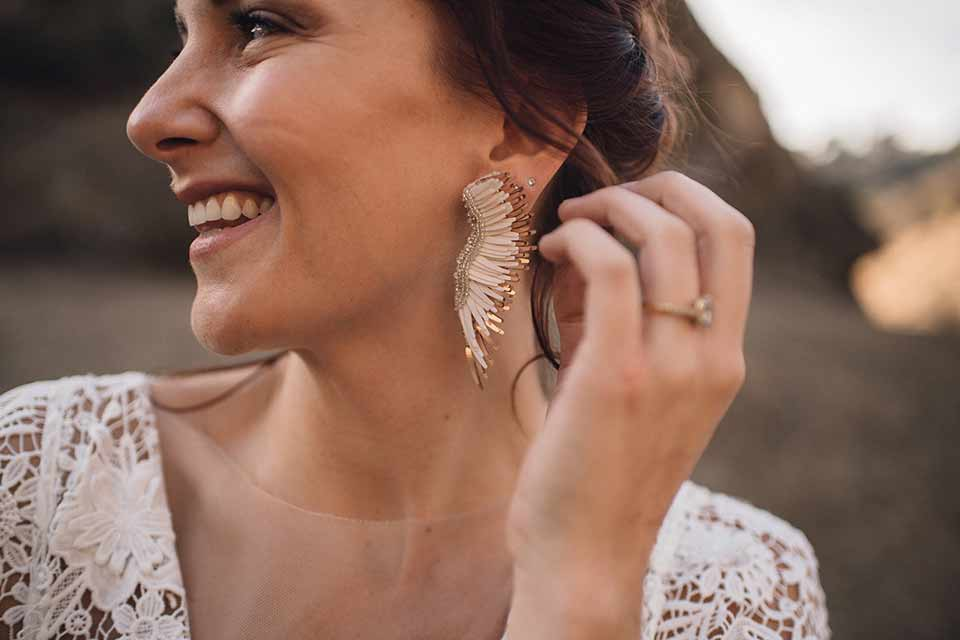 bronson-caves-elopement-shoot-close-up-on-bride-bride-wearing-a-lace-boho-inspired-dresswith-a-flowing-cape-detail-and-hair-up-in-a-mess-braided-bun