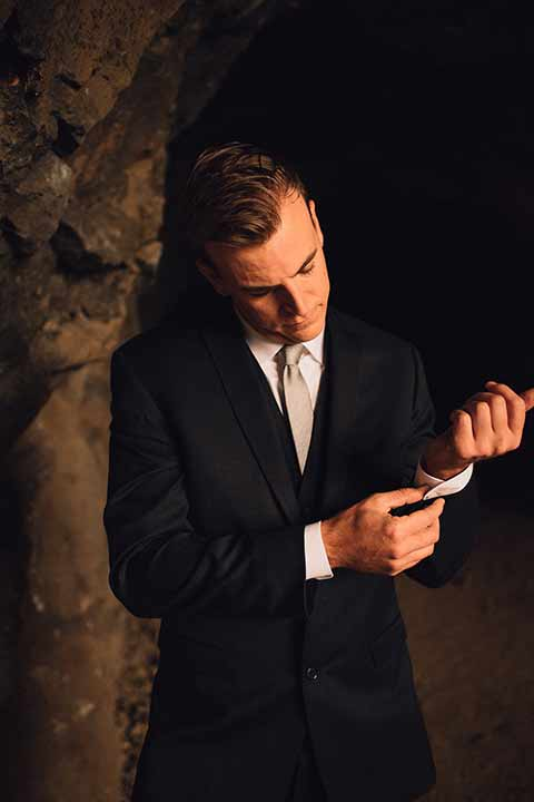 bronson-caves-elopement-shoot-groom-fixing-cuff-groom-in-cave-groom-wore-a-navy-suit-with-a-silver-tie