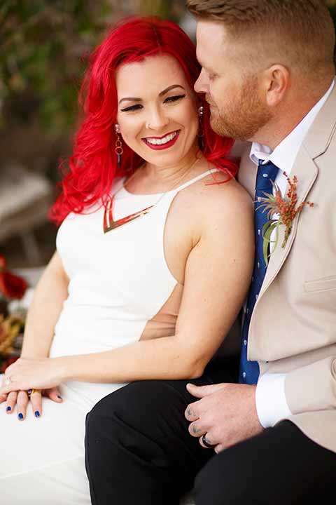 Desert-view-tower-bride-and-groom-close-up-smiling-bride-in-a-fitted-satin-dress-with-a-high-neckline-and-hot-pink-hair-groom-in-a-tan-coat-with-black-pants-and-a-blue-tie