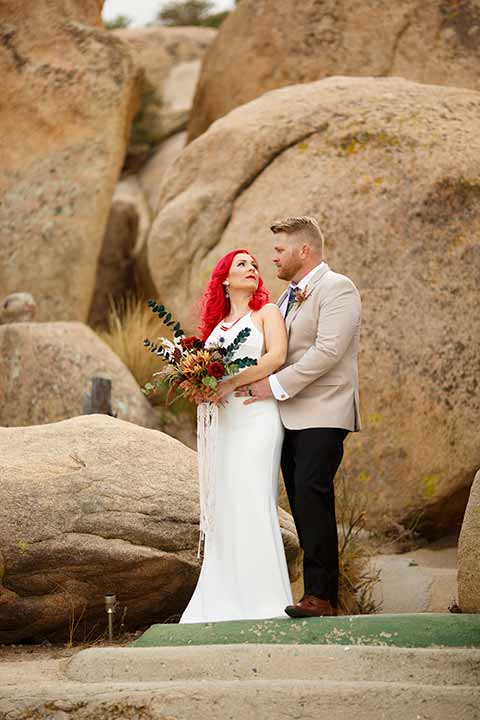Desert-view-tower-bride-and-groom-embrace-on-rock-bride-in-a-fitted-satin-dress-with-a-high-neckline-and-hot-pink-hair-groom-in-a-tan-coat-with-black-pants-and-a-blue-tie