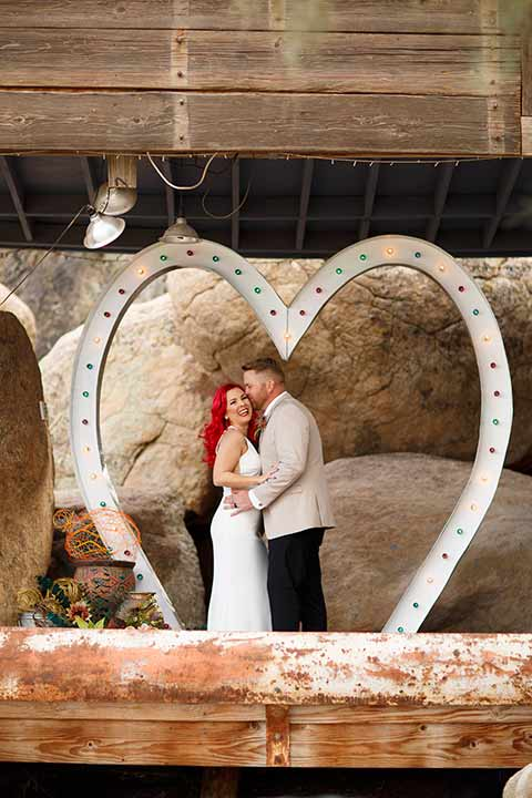Desert-view-tower-bride-and-groom-recetiption-laughing-bride-in-a-fitted-satin-dress-with-a-high-neckline-and-hot-pink-hair-groom-in-a-tan-coat-with-black-pants-and-a-blue-tie