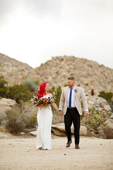 Desert-view-tower-bride-and-groom-holding-hands-bride-in-a-fitted-satin-dress-with-a-high-neckline-and-hot-pink-hair-groom-in-a-tan-coat-with-black-pants-and-a-blue-tie