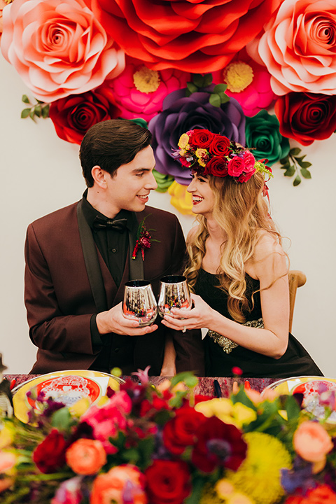 dia-de-los-muertos-cheers-bride-in-a-black-dress-with-floral-headpiece-groom-in-burgundy-tux-with-black-shirt-and-bow-tie