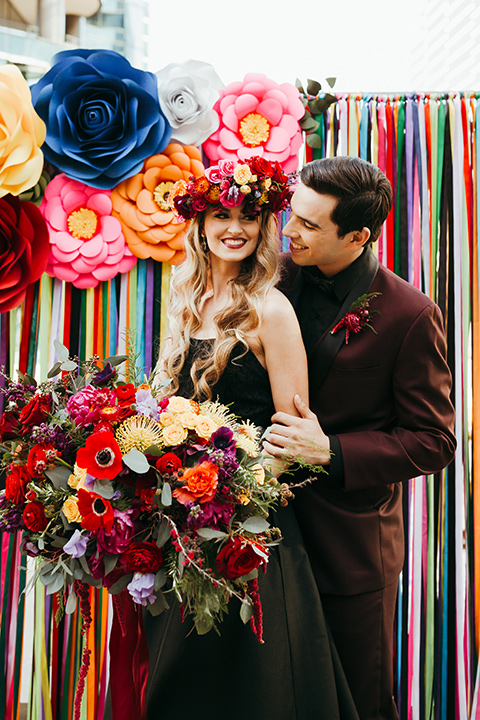 dia-de-los-muertos-color-background-bride-wearing-a-black-dress-and-floral-headpeice-groom-wearing-a-burgundy-tux-with-black-tri-and-black-shirt-with-black-bow-tie