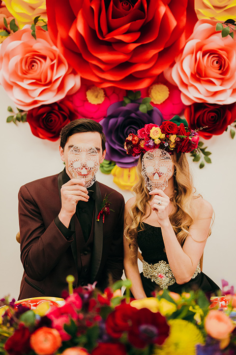 dia-de-los-muertos-drinking-bride-in-a-black-dress-with-floral-headpiece-groom-in-burgundy-tux-with-black-shirt-and-bow-tie