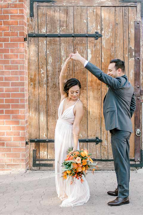 estate-on-second-shoot-bride-and-groom-dancing-bride-wearing-a-flowing-white-gown-with-thin-straps-and-hair-in-a-messy-boho-french-braid-groom-in-a-charcoal-grey-tuxedo-with-a-dark-brown-bow-and-shoes