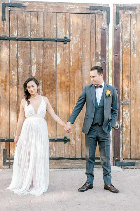 estate-on-second-shoot-bride-and-groom-holding-hands-bride-wearing-a-flowing-white-gown-with-thin-straps-and-hair-in-a-messy-boho-french-braid-groom-in-a-charcoal-grey-tuxedo-with-a-dark-brown-bow-and-shoes