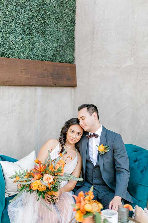 estate-on-second-shoot-bride-and-groom-on-blue-sofa-bride-looking-at-camera-bride-wearing-a-flowing-white-gown-with-thin-straps-and-hair-in-a-messy-boho-french-braid-groom-in-a-charcoal-grey-tuxedo-with-a-dark-brown-bow-and-shoes