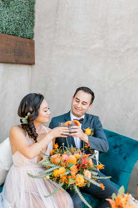 estate-on-second-shoot-bride-and-groom-on-blue-sofa-with-drinks-bride-wearing-a-flowing-white-gown-with-thin-straps-and-hair-in-a-messy-boho-french-braid-groom-in-a-charcoal-grey-tuxedo-with-a-dark-brown-bow-and-shoes
