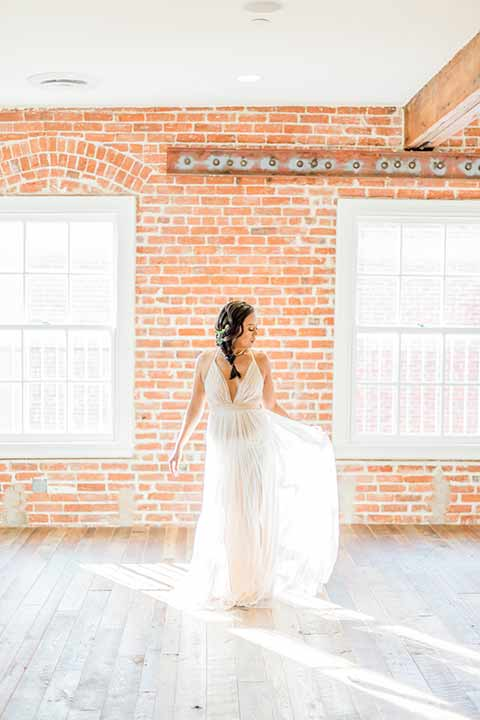 estate-on-second-shoot-bride-near-bricks-bride-wearing-a-flowing-white-gown-with-thin-straps-and-hair-in-a-messy-boho-french-braid