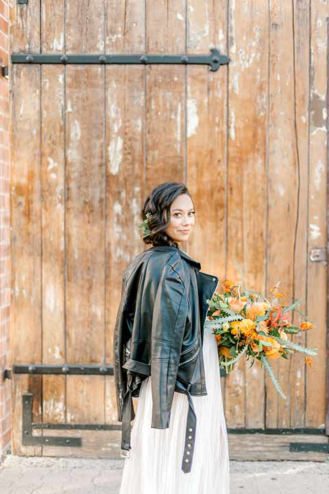 estate-on-second-shoot-bride-with-leather-jacket-bride-wearing-a-flowing-white-gown-with-thin-straps-and-hair-in-a-messy-boho-french-braid