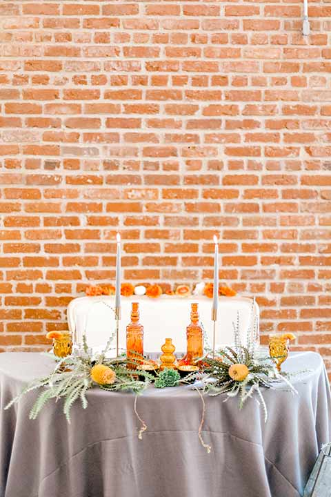 estate-on-second-shoot-sweetheart-table-grey-linens-with-the-brick-background-and-white-high-candles