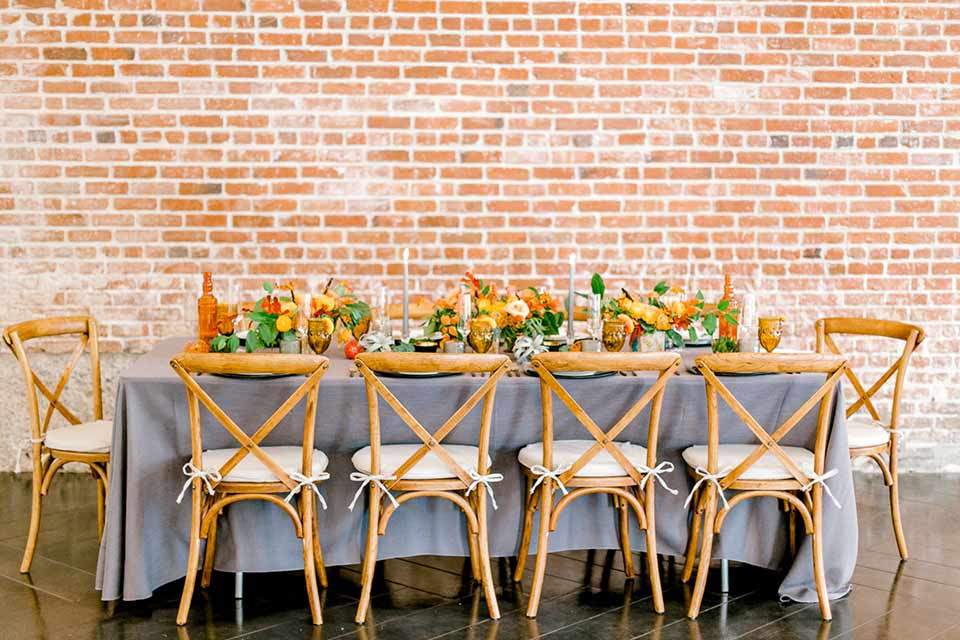 estate-on-second-shoot-table-set-up-brick-walls-wooden-chairs-and-grey-linen
