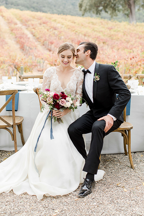 hammersky-editorial-shoot-bride-and-groom-sitting-bride-in-a-tulle-ballgown-with-lace-sleeves-and-high-neckline-groom-in-a-black-shawl-lapel-tuxedo-with-black-bow