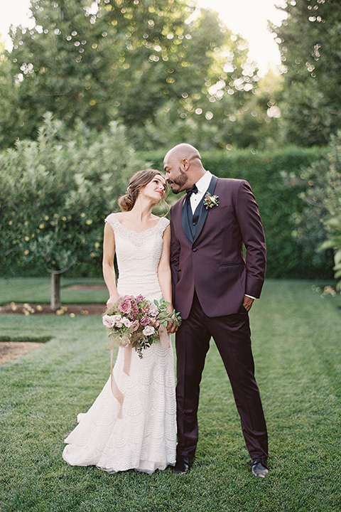 Kestrel-Park-venue-bride-and-groom-about-to-kiss-bride-alone-bride-in-a-fitted-gown-with-straps-and-lace-design-grom-in-a-burgundy-tuxedo-with-a-bow-tie
