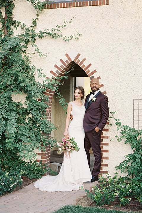 Kestrel-Park-venue-bride-and-groom-by-hedges-and-brick-wall-bride-in-a-fitted-gown-with-straps-and-lace-design-grom-in-a-burgundy-tuxedo-with-a-bow-tie