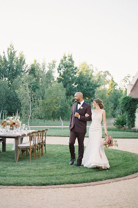 Kestrel-Park-venue-bride-and-groom-walking-by-table-bride-in-a-fitted-gown-with-straps-and-lace-design-grom-in-a-burgundy-tuxedo-with-a-bow-tie