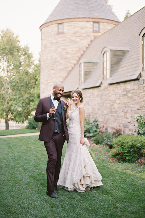 kestrel-park-venue-bride-and-groom-smiling-on-grass-bride-in-a-fitted-gown-with-straps-and-lace-design-grom-in-a-burgundy-tuxedo-with-a-bow-tie
