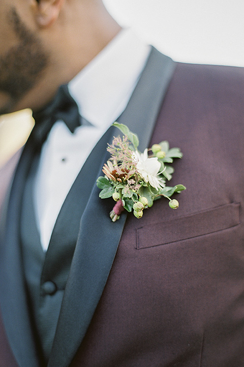 kestrel-park-venue-close-up-on-groom-jacket-in-a-fitted-gown-with-straps-and-lace-design-grom-in-a-burgundy-tuxedo-with-a-bow-tie