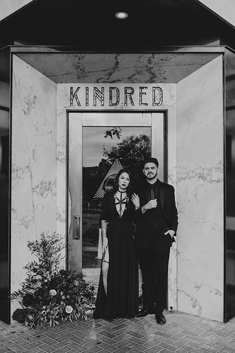 kindred-venue-gothic-inspired-shoot-b&w-photo-couple-in-front-of-doorway-bride-in-black-3/4-sleeve-dress-with-strap-and-metal-detailing-with-a-black-wide-brimmed-hat-groom-in-all-black-tuxedo-with-black-accessories