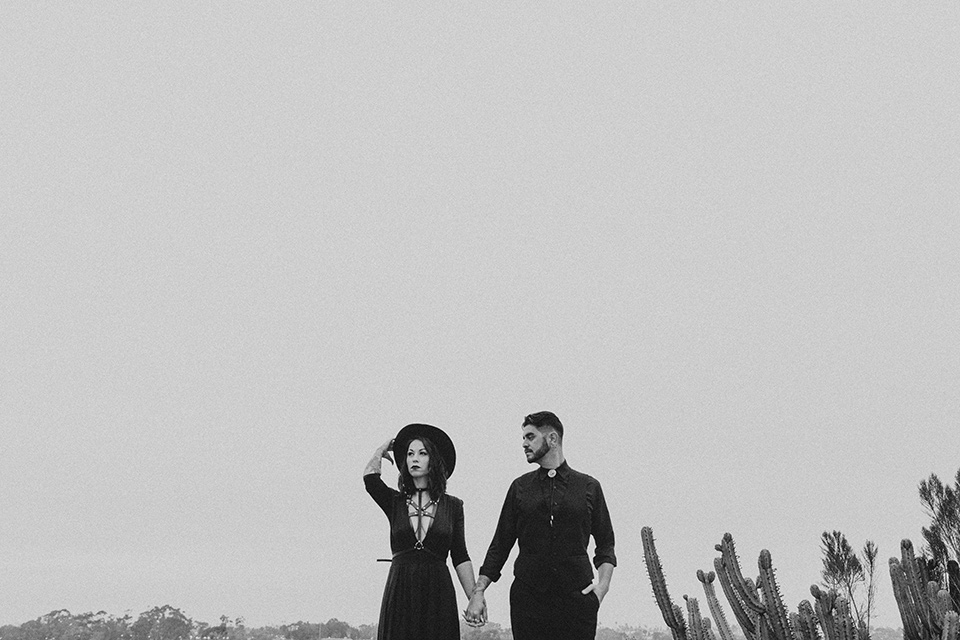 kindred-venue-gothic-inspired-shoot-back-and-white-photo-oh-bride-and-groom-waist-up-bride-in-black-3/4-sleeve-dress-with-strap-and-metal-detailing-with-a-black-wide-brimmed-hat-groom-in-all-black-tuxedo-with-black-accessories
