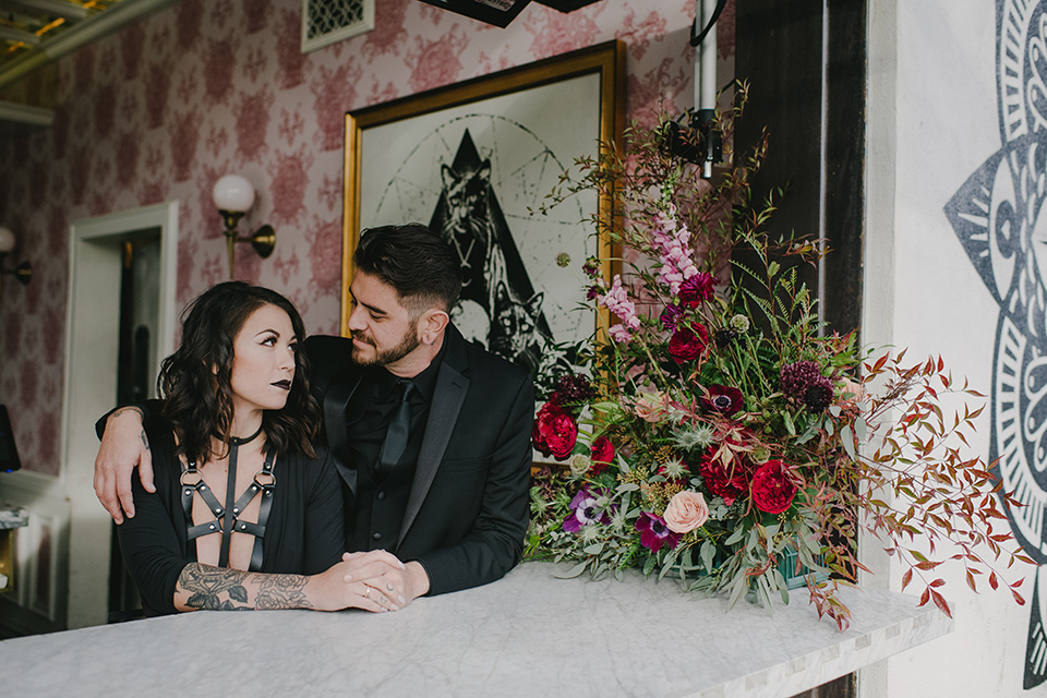 kindred-venue-gothic-inspired-shoot-bride-and-groom-at-bar-bride-in-black-3/4-sleeve-dress-with-strap-and-metal-detailing-with-a-black-wide-brimmed-hat-groom-in-all-black-tuxedo-with-black-accessories
