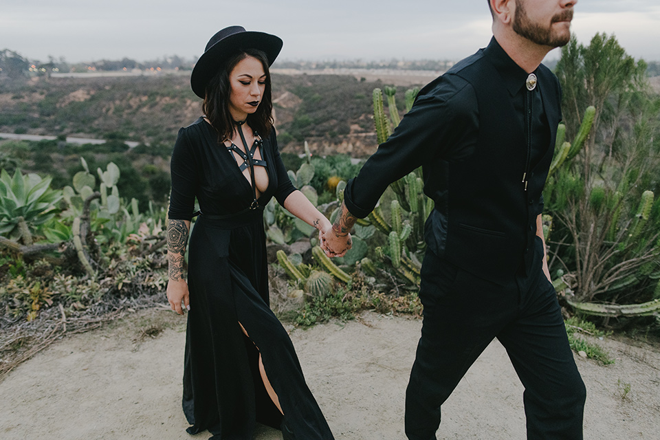 kindred-venue-gothic-inspired-shoot-bride-and-groom-walking-outside-with-canon-behind-them-bride-in-black-3/4-sleeve-dress-with-strap-and-metal-detailing-with-a-black-wide-brimmed-hat-groom-in-all-black-tuxedo-with-black-accessories