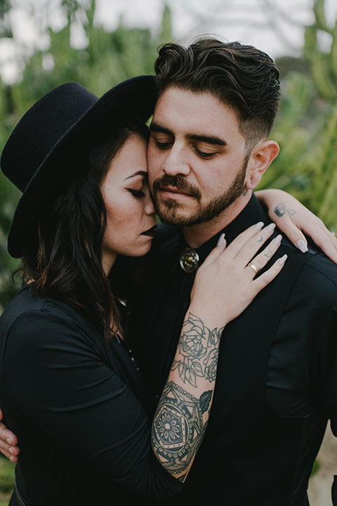kindred-venue-gothic-inspired-shoot-close-up-of-bride-and-groom-touching-heads-outside-bride-in-black-3/4-sleeve-dress-with-strap-and-metal-detailing-with-a-black-wide-brimmed-hat-groom-in-all-black-tuxedo-with-black-accessories