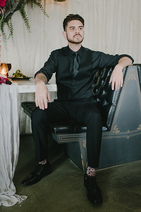 kindred-venue-gothic-inspired-shoot-groom-in-booth-groom-in-all-black-tuxedo-with-black-accessories