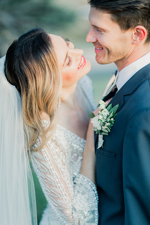 MUCKENTHALER-SHOOT-bride-and-groom-close-up-smiling-bride-in-fitted-satin-long-sleeve-gown-groom-in-a-slate-blue-suit-with-a-ivory-bow-tie