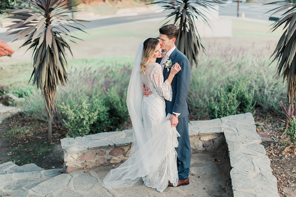 MUCKENTHALER-SHOOT-bride-and-groom-embrace-bride-in-fitted-satin-long-sleeve-gown-groom-in-a-slate-blue-suit-with-a-ivory-bow-tie