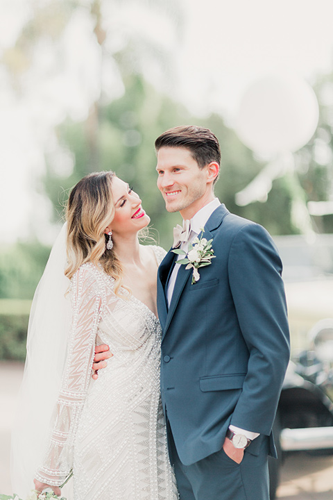 MUCKENTHALER-SHOOT-bride-and-groom-laughing-bride-in-fitted-satin-long-sleeve-gown-groom-in-a-slate-blue-suit-with-a-ivory-bow-tie