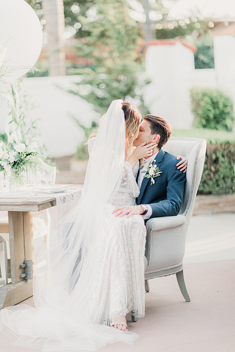 MUCKENTHALER-SHOOT-bride-and-groom-sitting-in-chair-bride-in-fitted-satin-long-sleeve-gown-groom-in-a-slate-blue-suit-with-a-ivory-bow-tie