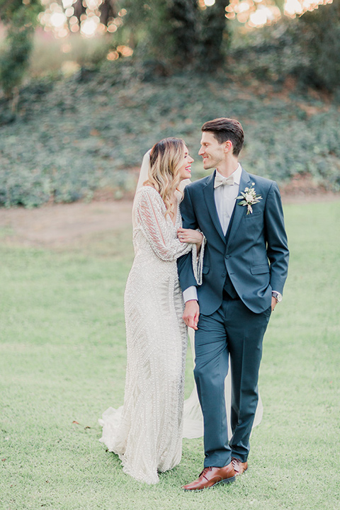 MUCKENTHALER-SHOOT-bride-and-groom-walking-connected-hand-in-hand-bride-in-fitted-satin-long-sleeve-gown-groom-in-a-slate-blue-suit-with-a-ivory-bow-tie