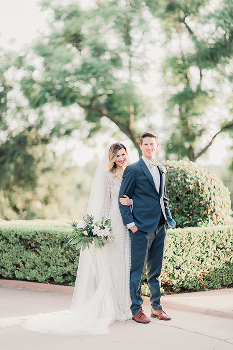 MUCKENTHALER-SHOOT-bride-standing-behind-groom-bride-in-fitted-satin-long-sleeve-gown-groom-in-a-slate-blue-suit-with-a-ivory-bow-tie