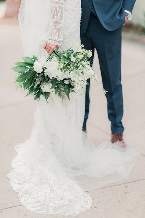MUCKENTHALER-SHOOT-close-up-on-bride-and-groom-clothing-bride-in-fitted-satin-long-sleeve-gown-groom-in-a-slate-blue-suit-with-a-ivory-bow-tie