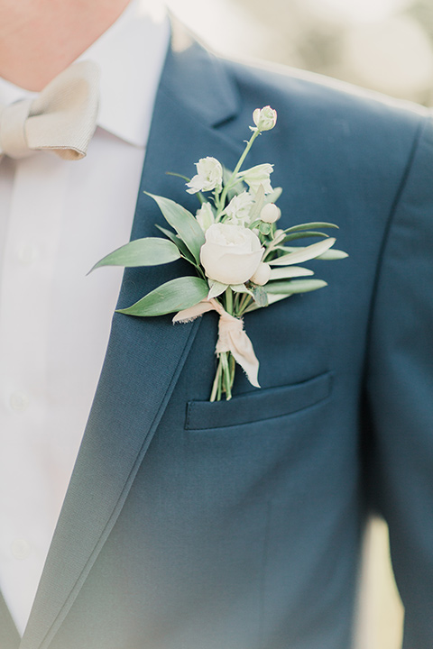 MUCKENTHALER-SHOOT-close-up-on-coat-groom-in-a-slate-blue-suit-with-a-ivory-bow-tie