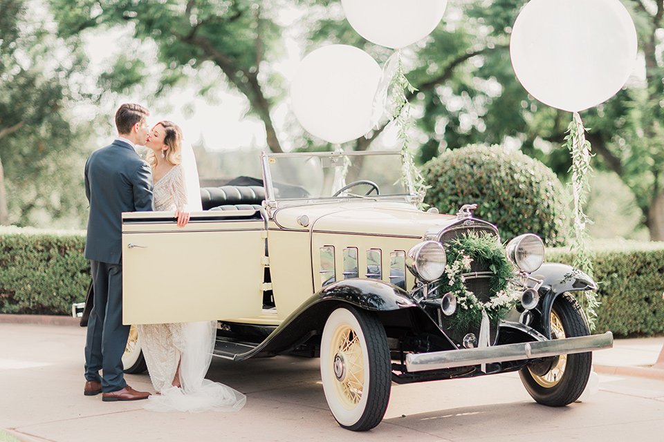 MUCKENTHALER-SHOOT-couple-by-car-bride-in-fitted-satin-long-sleeve-gown-groom-in-a-slate-blue-suit-with-a-ivory-bow-tie
