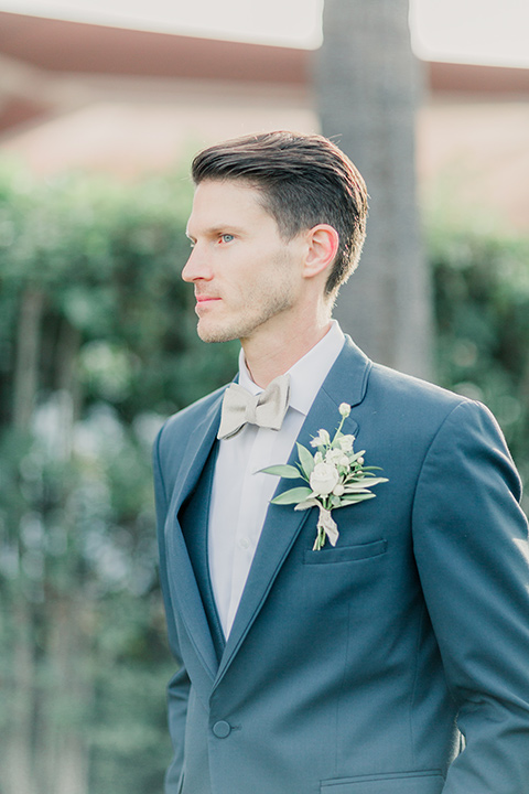 MUCKENTHALER-SHOOT-groom-groom-in-a-slate-blue-suit-with-a-ivory-bow-tie