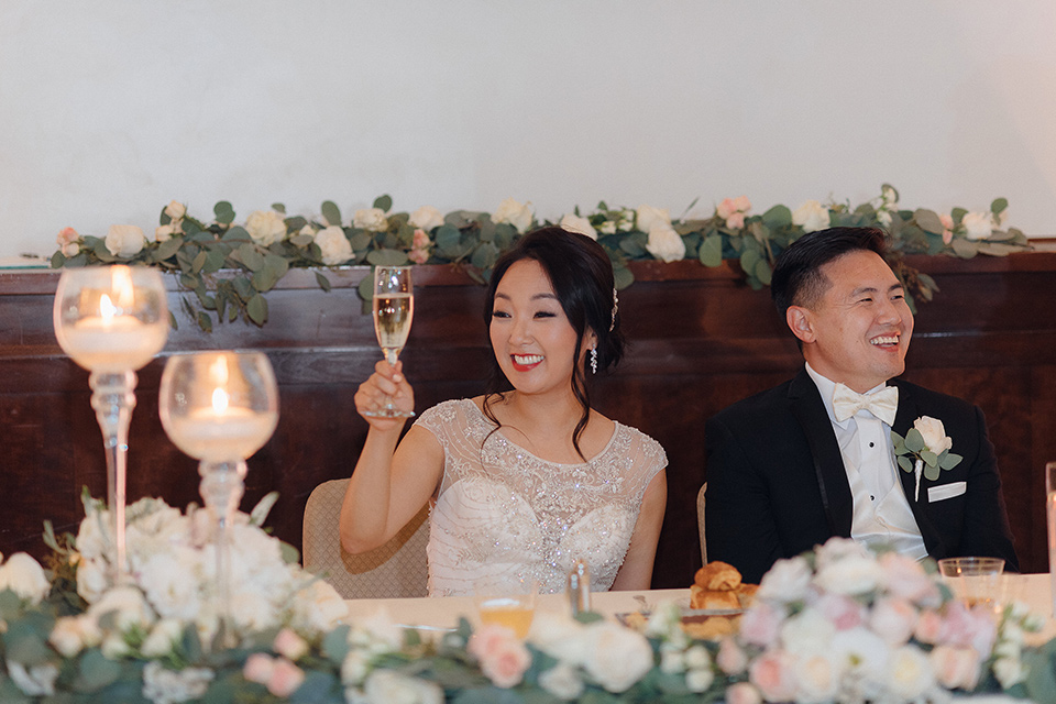 occidental-college-wedding-bride-and-groom-at-sweetheart-table-groom-in-black-tuxedo-bride-in-a-fitted-gown-with-a-beaded-bodice-bridesmaids-in-blue-gowns