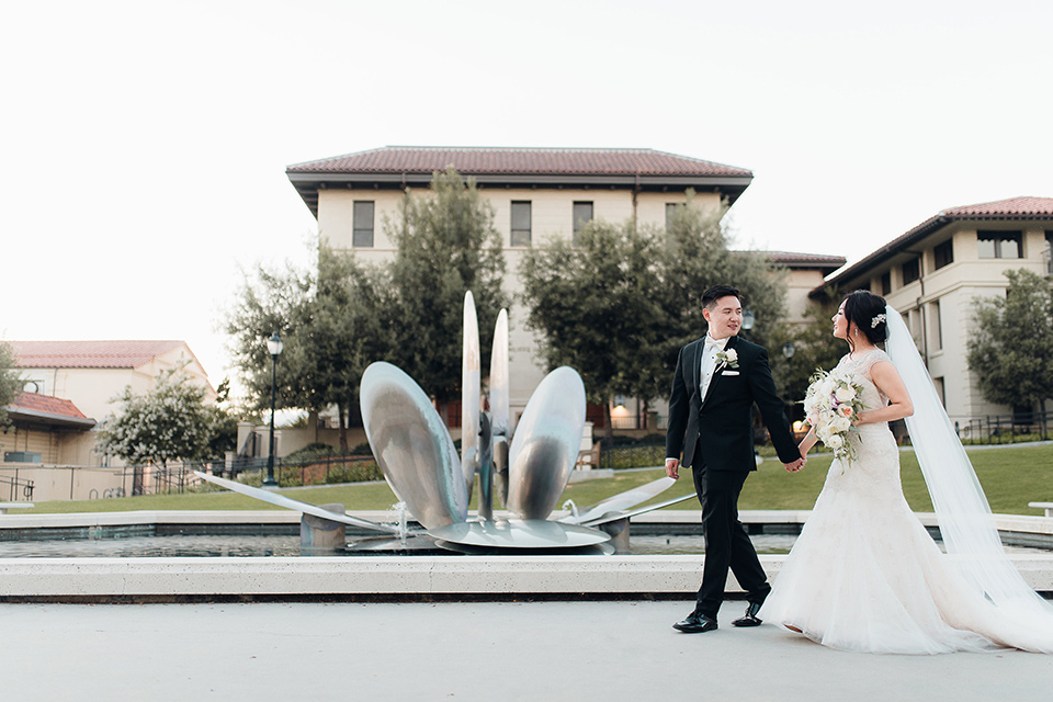 occidental-college-wedding-bride-and-groom-walking-by-fountain-groom-in-black-tuxedo-bride-in-a-fitted-gown-with-a-beaded-bodice